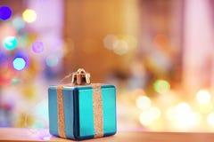 Tarjeta del Año Nuevo con el juguete bajo la forma de regalo con una cinta en un fondo de las luces borrosas del árbol de navidad Fotografía de archivo