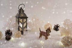 Tarjeta del Año Nuevo con el perro de juguete en un bosque de hadas en fondo del invierno Fotografía de archivo libre de regalías