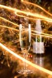 Tarjeta del Año Nuevo con el vidrio y las chispas del champán Fotografía de archivo libre de regalías