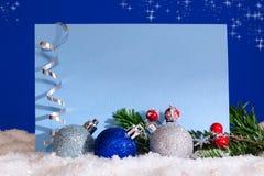 Tarjeta del Año Nuevo con las bolas de la Navidad en la nieve Fotos de archivo libres de regalías