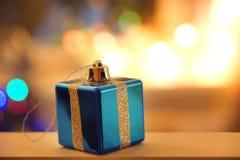Tarjeta del Año Nuevo con un juguete bajo la forma de regalo azul en el fondo de las luces borrosas del árbol de navidad Imágenes de archivo libres de regalías