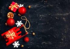 Tarjeta del Año Nuevo de la Navidad del día de fiesta, trineo rojo del juguete, bolas, caja de regalo Foto de archivo