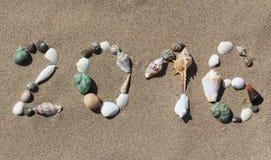 Tarjeta del Año Nuevo En una playa arenosa del cuadro 2016 de cáscaras Imagen de archivo libre de regalías