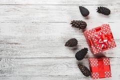 Tarjeta del Año Nuevo, regalo envuelto en el empaquetado rojo con los conos decorativos coloreados del pino Fotos de archivo