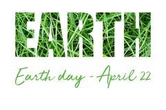 Tarjeta del concepto con la inscripción del Día de la Tierra en hierba verde Fotos de archivo libres de regalías
