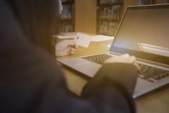 Tarjeta del control de la mujer a disposición y ordenador portátil del uso en la tabla de madera imágenes de archivo libres de regalías