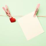 Tarjeta del corazón y de felicitación atada con una pinza Foto de archivo libre de regalías