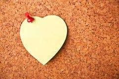 Tarjeta del corcho con el post-it del corazón Imagen de archivo
