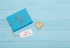 Tarjeta del día de madres, caja de regalo y corazón en fondo azul Imágenes de archivo libres de regalías