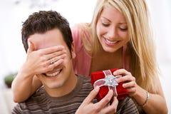Tarjeta del día de San Valentín: La mujer sorprende al hombre con el regalo Foto de archivo