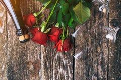 Tarjeta del día de tarjetas del día de San Valentín Rosas rojas hermosas Composición plana de la endecha Botella de champán Visió fotos de archivo