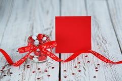 Tarjeta del día del ` s de la tarjeta del día de San Valentín con el tarro colorido del caramelo adornado con un arco rojo en fon Imagen de archivo