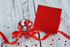 Tarjeta del día del ` s de la tarjeta del día de San Valentín con el tarro colorido del caramelo adornado con un arco rojo en fon Fotografía de archivo