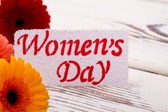 Tarjeta del día del ` s de las mujeres cerca de gerberas Foto de archivo libre de regalías