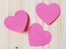 Tarjeta del día de tarjetas del día de San Valentín con la nota pegajosa en la forma de un corazón en un fondo de madera Imágenes de archivo libres de regalías