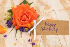 Tarjeta del feliz cumpleaños con el manojo hermoso de flor color de rosa en fondo de madera Fotos de archivo