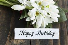 Tarjeta del feliz cumpleaños con el ramo de Snowdrops Imagen de archivo