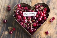 Tarjeta del feliz cumpleaños con las cerezas en el molde para pasteles del corazón Foto de archivo libre de regalías