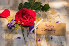 Tarjeta del feliz cumpleaños con las flores en la madera rústica Imagen de archivo