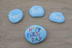 Tarjeta del feliz cumpleaños con las piedras talladas y coloreadas sobre la arena de la playa Fotos de archivo libres de regalías