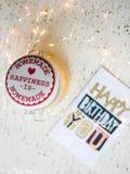Tarjeta del feliz cumpleaños en una tabla y luces de la Navidad Foto de archivo libre de regalías