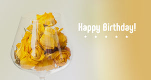 Tarjeta del feliz cumpleaños Flores color de rosa secadas en la copa de vino, fondo beige de la pendiente pétalos amarillos visió Foto de archivo