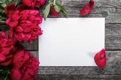 Tarjeta del Libro Blanco en fondo de madera rústico con las peonías y los pétalos rosados Flores workspace Imagen de archivo