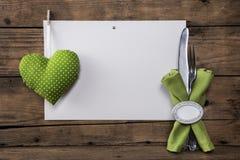 Tarjeta del menú con un corazón verde y lunares blancos más los cubiertos a imagen de archivo