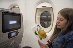 Tarjeta del menú de la lectura del viajero de la mujer joven a bordo Fotografía de archivo