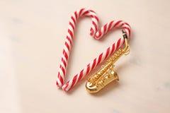 Tarjeta del ` s del Año Nuevo - bastón de oro del saxofón y de caramelo Backgro blanco Foto de archivo