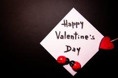 Tarjeta del ` s de la tarjeta del día de San Valentín en un fondo negro Foto de archivo libre de regalías