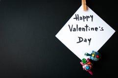 Tarjeta del ` s de la tarjeta del día de San Valentín en una tierra de la parte posterior del negro Fotografía de archivo