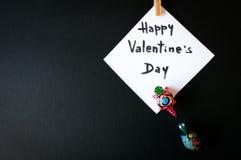 Tarjeta del ` s de la tarjeta del día de San Valentín en una tierra de la parte posterior del negro Imagen de archivo libre de regalías
