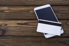 Tarjeta del teléfono y del plástico en el fondo de madera de la tabla imágenes de archivo libres de regalías