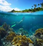 Tarjeta del viaje con una mujer que flota en una isla y un coral tropicales Foto de archivo