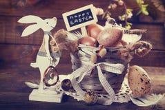 Tarjeta del vintage con los huevos de Pascua en la cesta vieja y el conejo divertido diciembre Fotos de archivo