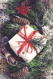 Tarjeta del vintage de la Navidad Caja de regalo festiva, ramas coníferas a Fotos de archivo