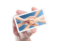 Tarjeta del voluntario de la tenencia de la mano con las manos unidas como fondo Fotos de archivo libres de regalías