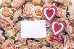 Tarjeta en blanco blanca con los corazones decorativos en el fondo del perno Fotos de archivo