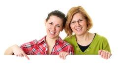 Tarjeta en blanco blanca de los asimientos de la madre y de la hija imágenes de archivo libres de regalías