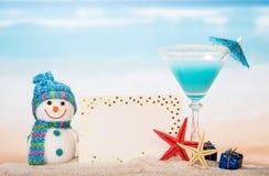 Tarjeta en blanco, cóctel, muñeco de nieve y regalos en arena contra el mar Fotos de archivo libres de regalías