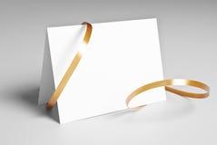 Tarjeta en blanco con la cinta de oro Imagenes de archivo