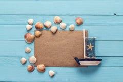 Tarjeta en blanco con las conchas marinas y un barco de navegación decorativo en azul Fotos de archivo libres de regalías