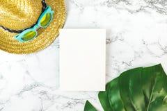 Tarjeta en blanco del Libro Blanco en la opinión de sobremesa de mármol con el beac del verano Fotografía de archivo