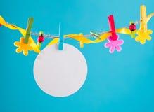 Tarjeta en blanco fijada en cuerda para tender la ropa Copie el espacio para la fraseología Fijado con los pernos de la flor Fond Foto de archivo libre de regalías