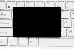 Tarjeta en blanco negra vacía en el teclado de ordenador Imagen de archivo libre de regalías