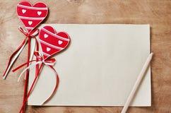 Tarjeta en blanco y corazones rojos de madera en una tabla de madera fotos de archivo libres de regalías