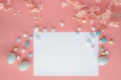 Tarjeta en blanco y flores de Pascua de los huevos del caramelo en colores pastel de la malta sobre Coral Colored Background fotos de archivo libres de regalías