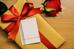 Tarjeta en la caja de regalo de la cinta y la rosa del rojo Imagenes de archivo