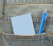 Tarjeta en un bolsillo trasero de vaqueros del dril de algodón como fondo Foto de archivo